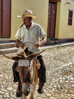 Cuban man on top a donkey